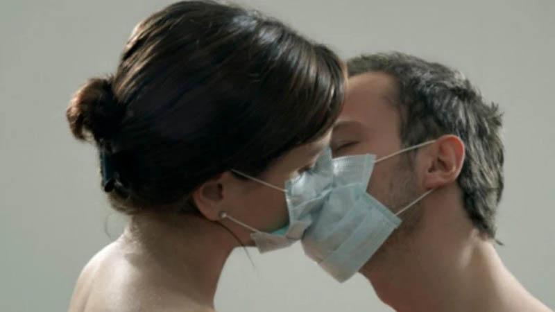 Um casal de máscara se beijando